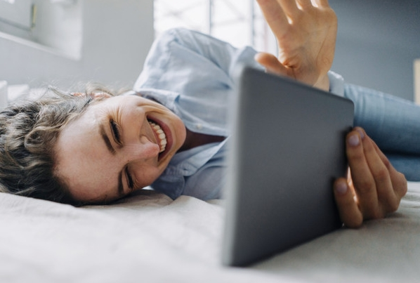 girl on bed with tablet